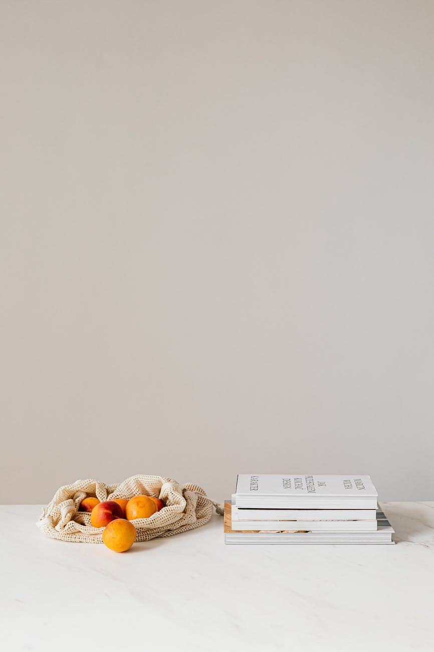 cotton sack with apricots near books on table