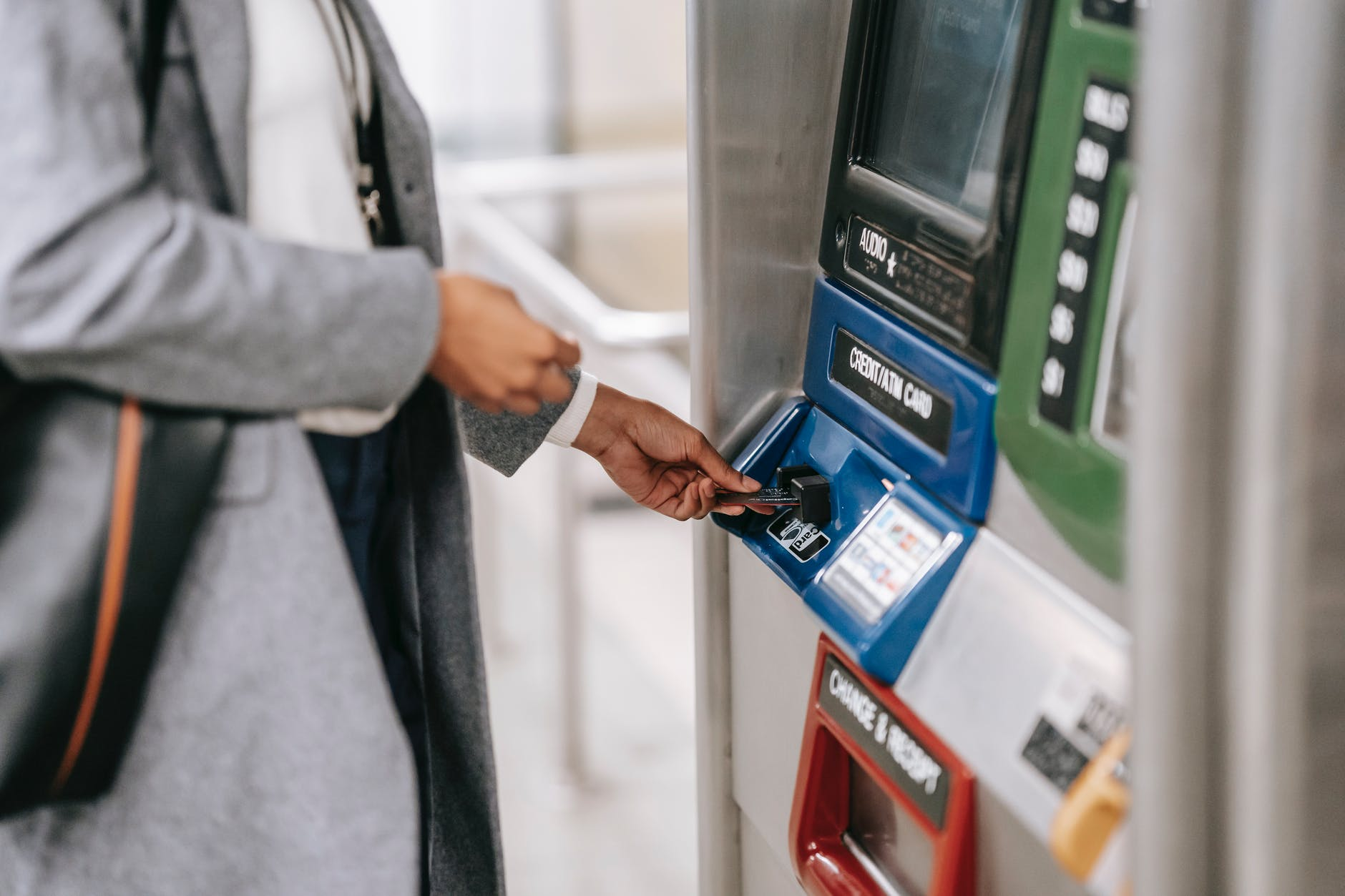 faceless woman inserting credit card into subway ticket machine